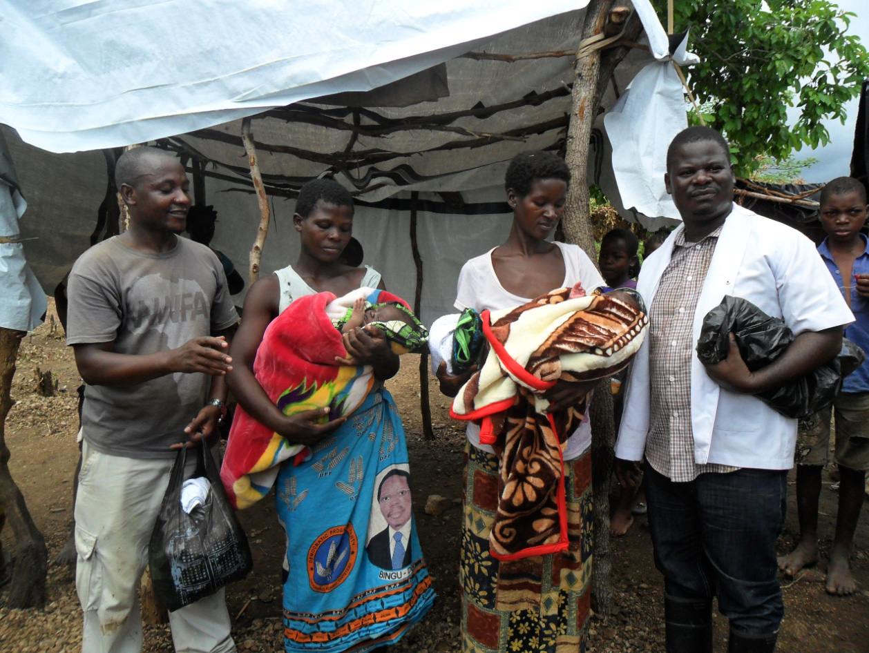 """Edwin, on the left, along with Isaac (right) give much needed blankets to two new mothers. Edwin named the baby on the left who was born in a church """"David"""" and Isaac named the one """"Joshua"""" who was born in a tree during the flood. Isaac said, """"He needs to be strong and courageous—like Joshua in the Bible—in order to survive."""""""