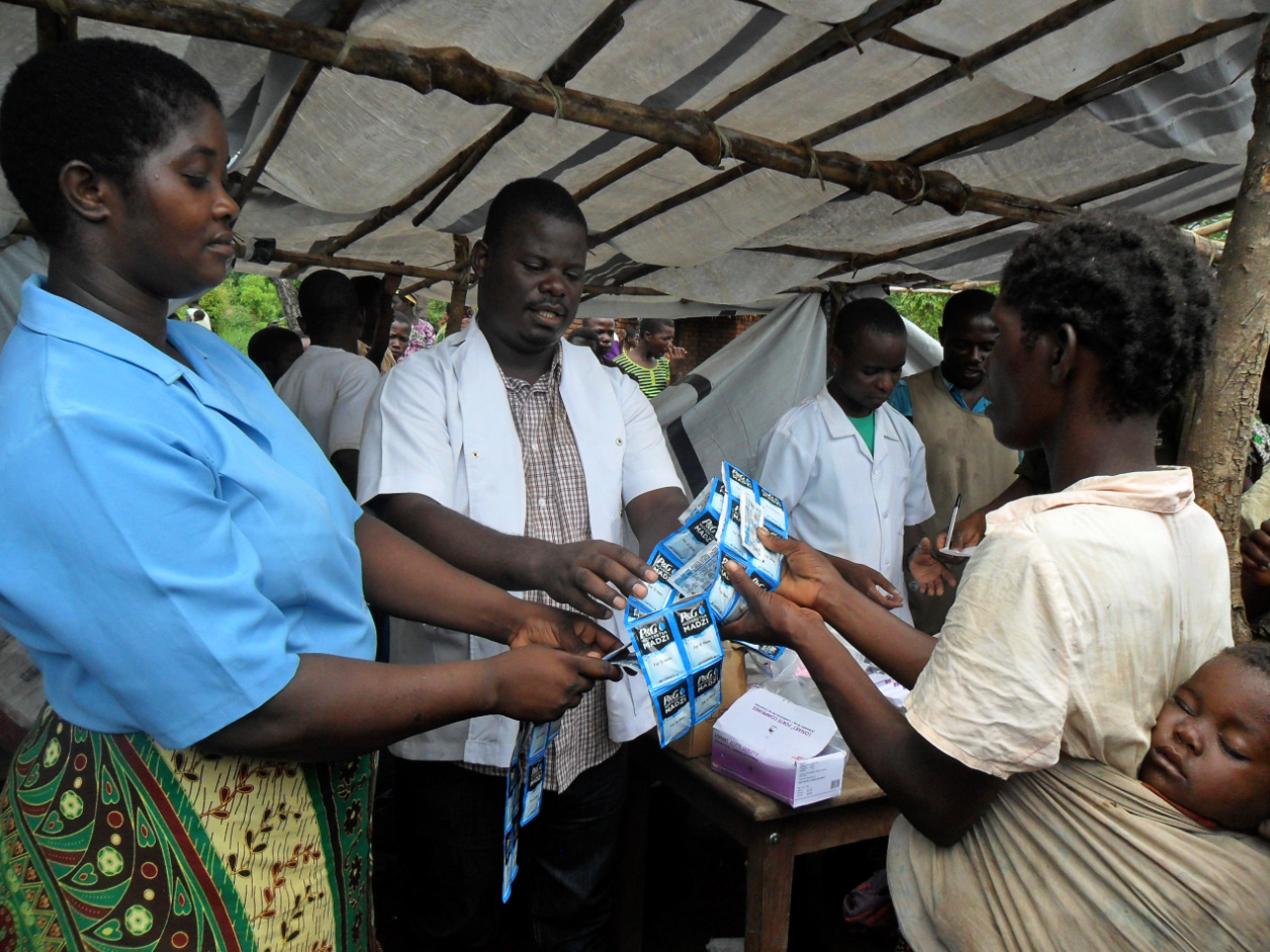 Isaac distributes water treatment packets, purchased by donations to WWFA, to our friends stranded in at the Osiyana refugee camp.