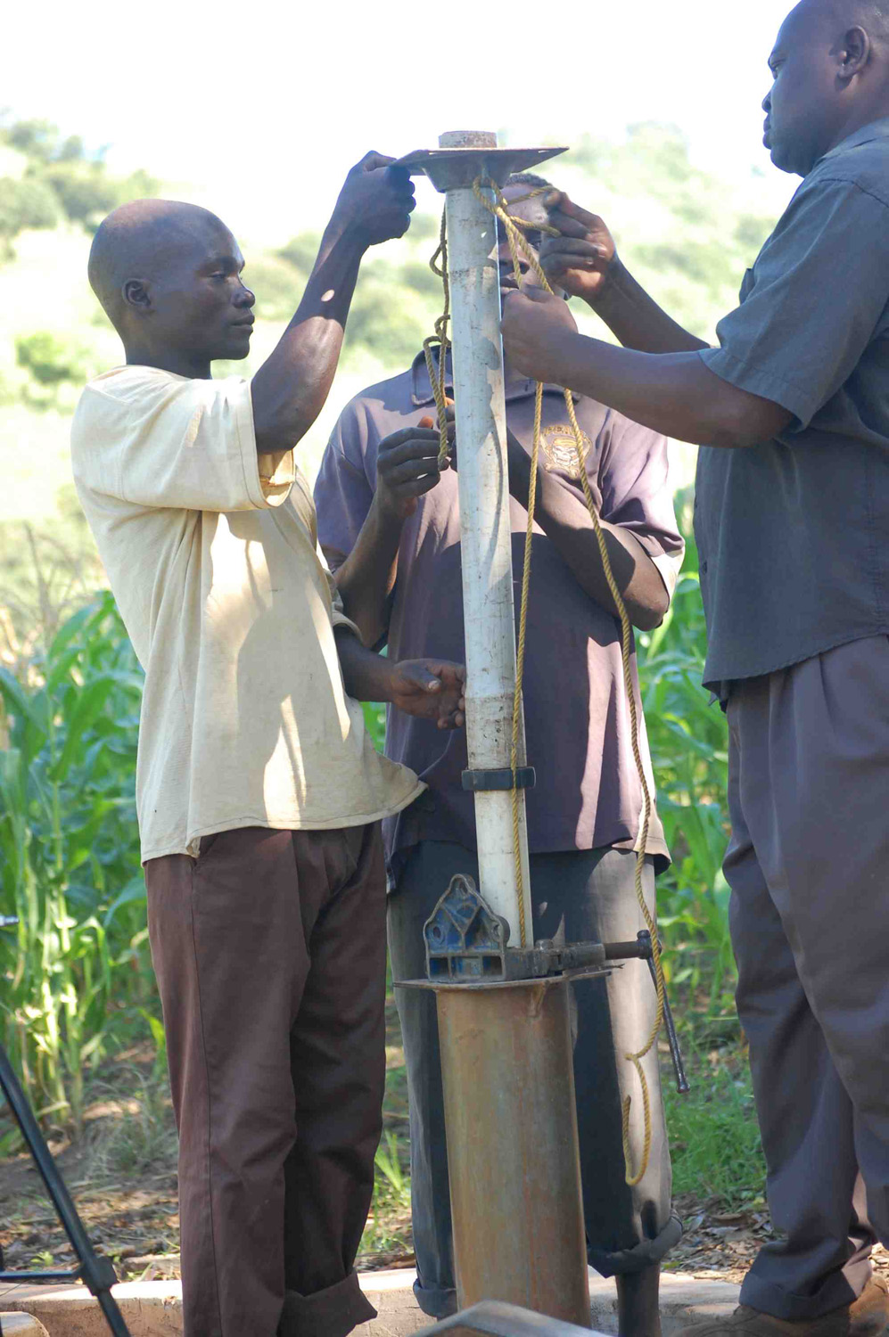 Community members taking part in fixing the borehole.