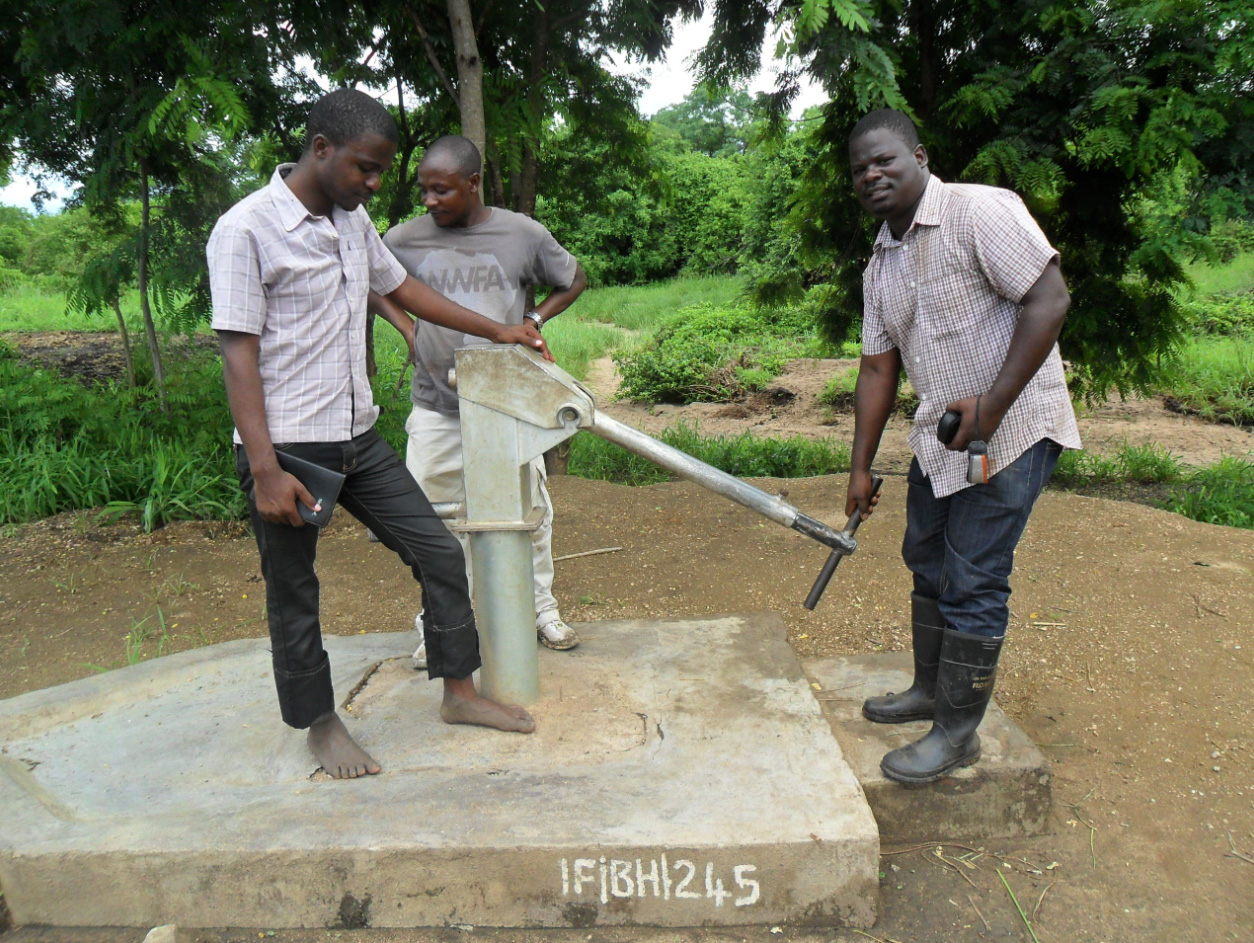 Edwin in the back and Isaac on the right inspect a broken borehole with a local leader. Edwin has taken with him 25kgs of chlorine to sanitize and tools to repair any boreholes he might find in the area. Unfortunately, there is no borehole near the refugee camp.